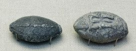 "Ancient Greek lead sling bullets with a winged thunderbolt engraved on one side and the inscription ""ΔΕΞΑΙ"" (Dexai) meaning ""take that"" or ""catch"" on the other side, 4th century BC, from Athens, British Museum."