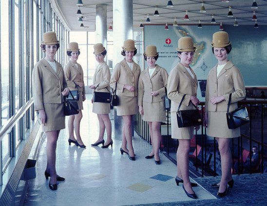 A group of air hostesses wearing identical clothes and accessories.