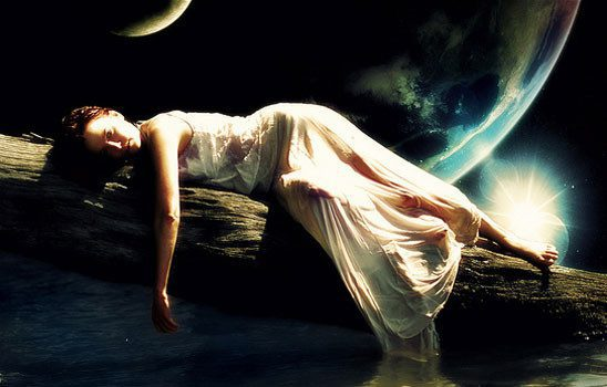 A woman in gauzy white drapes over a tree trunk with planets in the sky behind her