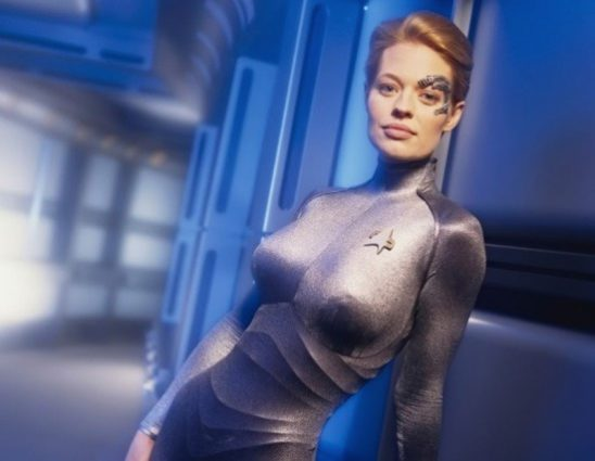 Seven posing in sexy position in tight silver catsuit