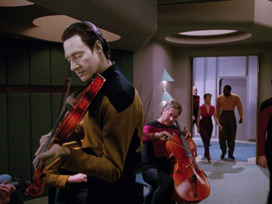 Data getting ready to play the violin.