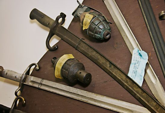 Antique swords and grenades laid out with yellow and blue labels