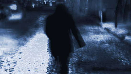A man silhouetted on a dark street.