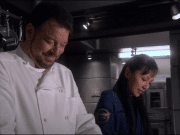 Riker dresshed as Chef talking to Hoshi.