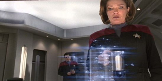 Janeway standing in front of a replicator.