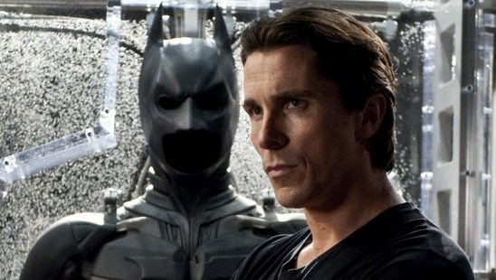Christian Bale standing beside the Batsuit.