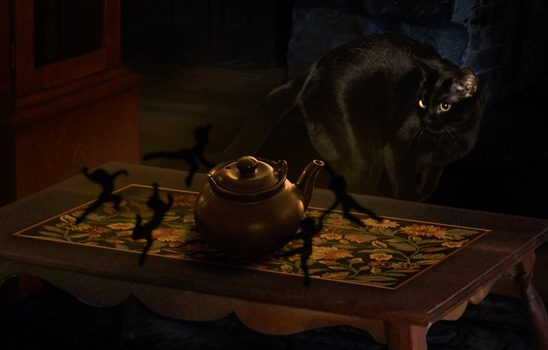 A black cat looks on as small shadow creatures circle a teapot