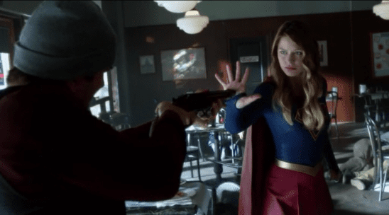 Supergirl putting her hand over a criminal's shotgun.