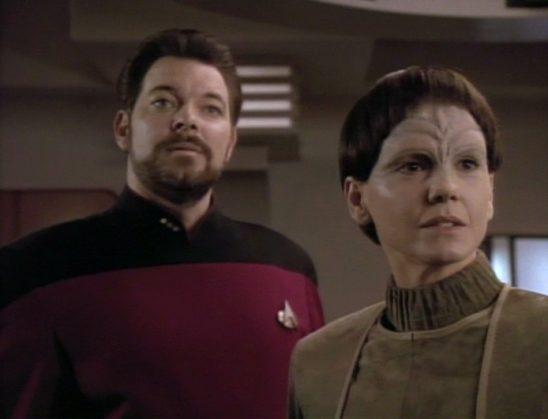 Riker stands behind Soren, a woman who has to keep her gender secret