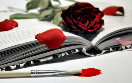 Rose and rose petals on a book next to a brush with red paint