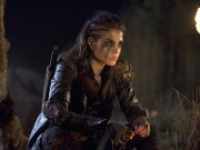 Octavia Blake from the 100 sits before a fire.