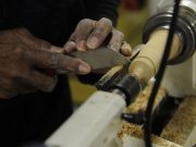 A woodworker shaping a chair leg.
