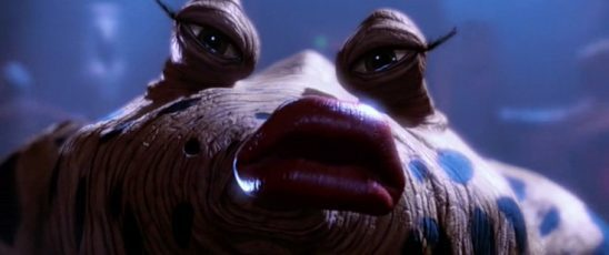 An alien with a long snout and protruding eyes has red lipstick and long eyelashes