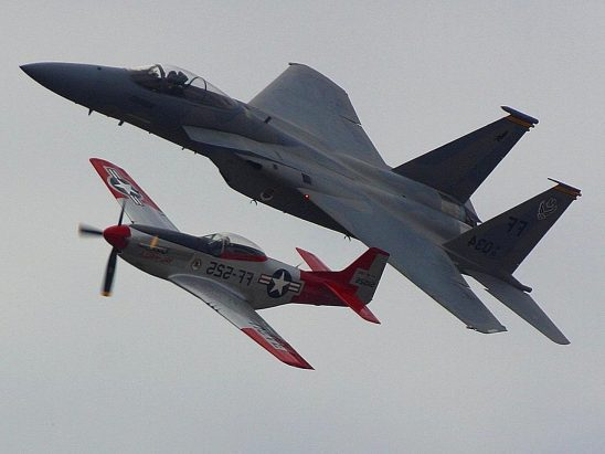 An F-15 jet flying alongside a P51 Mustang