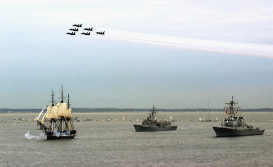 The USS Constitution escorted by modern naval ships.