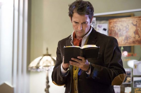 Flynn looking in a book from The Librarians.