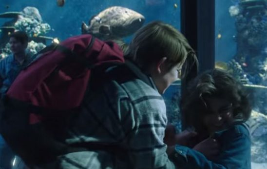 An older boy pins a younger boy against an aquarium tank.