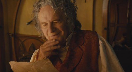 Bilbo from Lord of the Rings looking at a page of his writing.