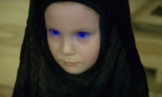 A girl in a black robe with glowing blue eyes