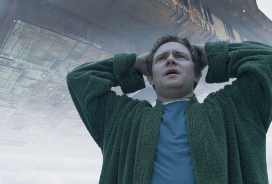 Arthur Dent looks distraught as a huge alien ship looms behind him