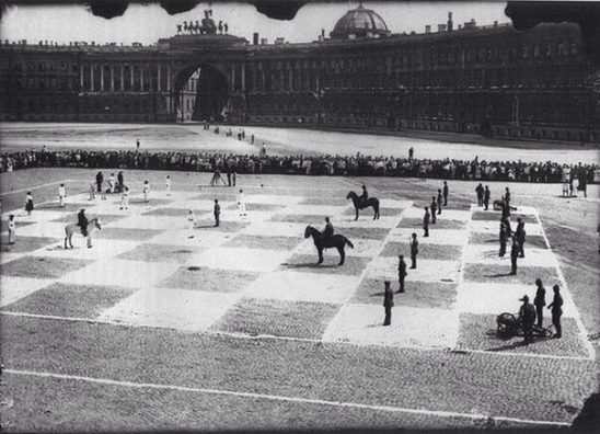 "A black and white game of ""human chess,"" complete with cannons and horses."
