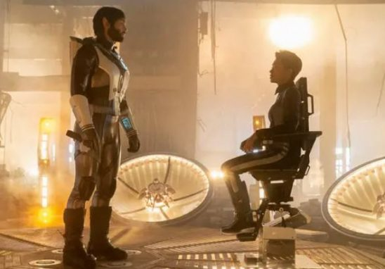 Spock stands facing Michael, who is strapped in a chair