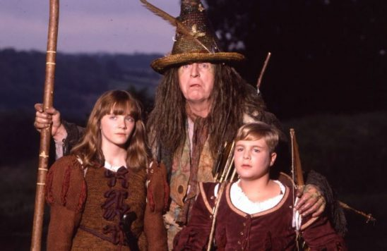 Two children and an odd-looking man in fantasy clothes