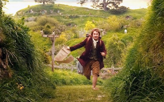 Bilbo the hobbit runs out of town with a sheet of parchment