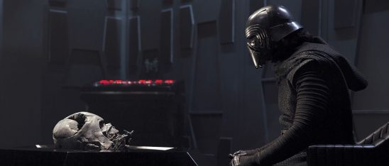 Kylo Ren looking at Vader's mask.