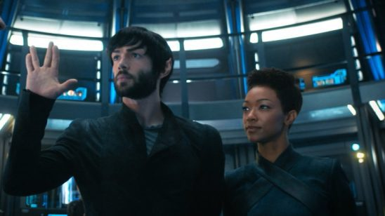 Spock and Burnham standing close together with Spock holding up the Vulcan Salute.