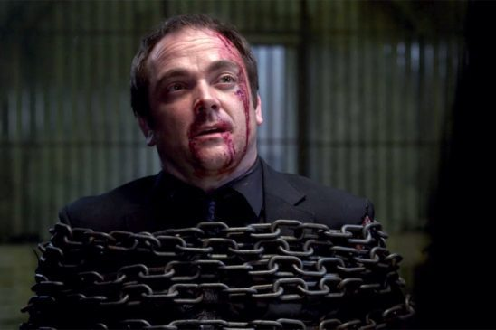 Crowley with a bloody face, restrained by chains in Supernatural.