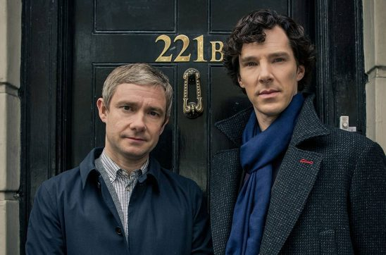 Benedict Cumberbatch playing a tall dark Holmes standing next to Martin Freeman's shorter blond Watson