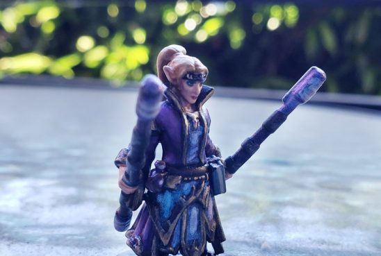 A miniature of an elven wizard holding her two staves at the ready