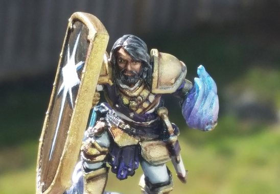 A miniature of a warrior wielding a blue flame crouching behind his shield