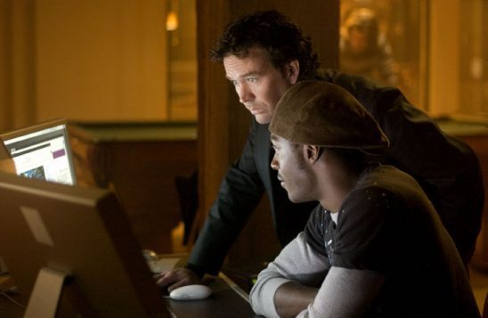 A black man and a white man look at a couple monitors