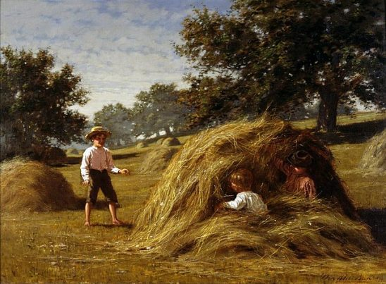 Two kids hiding from a third kid in a hay pile.