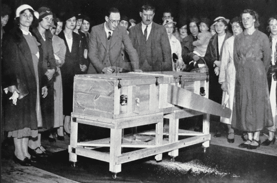 A black and white photo of a magician sawing a box in half.