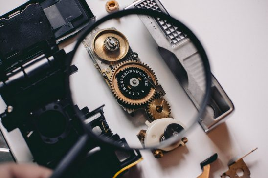 A set of watch gears shown through a magnifying glass.