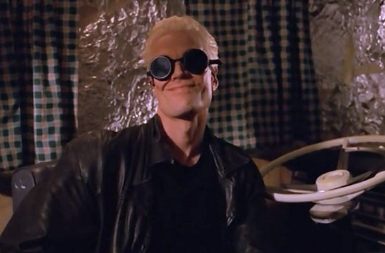 A pale man with dark goggles sites behind a driver's wheel.