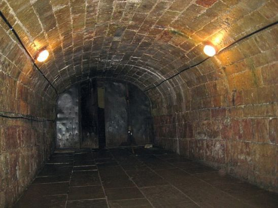 A brick tunnel lit with electric lights.
