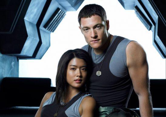 A woman leans against a man inside a spaceship