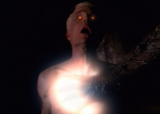 A man with glowing eye cries out in pain as a hand glows on his chest