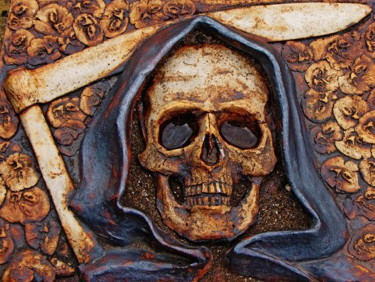 A stone carving of death with a skull face and scythe.