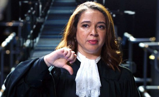 A Hispanic woman in a judge's robe holding a thumbs down