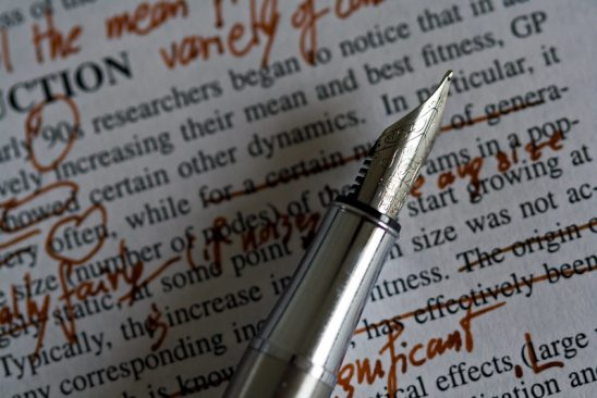 A silver pen on a page of marked up text.