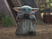 Baby Yoda stands outside holding a cup.