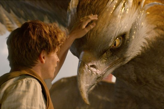 A white man pets the head of a giant eagle creature