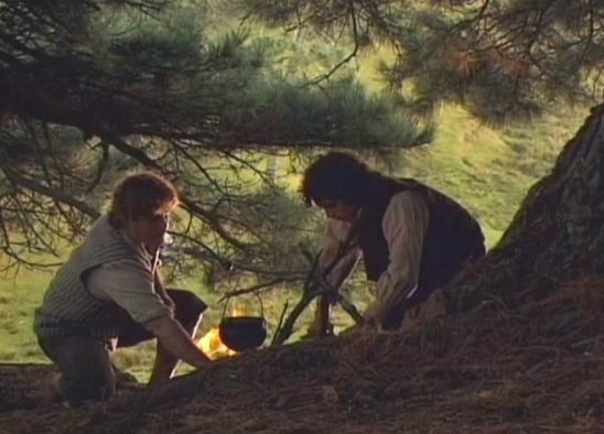 Sam and Frodo sitting at a camp fire.