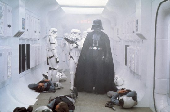 Darth Vader and stormtroopers in a smokey ship hallway with dead rebels on the floor.