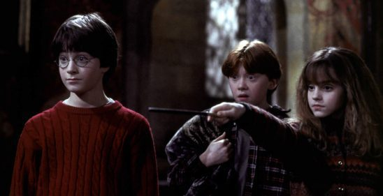 Harry and Ron looking on in awe as Hermione points her wand.